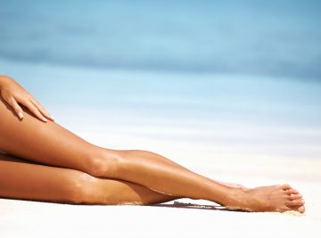 Glamorous woman with perfect legs relaxing on a sunlit beach
